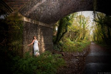a bride leaning against the wall in the archway under a bridge in Crackley Woods, Kenilworth
