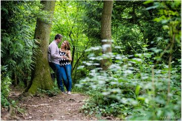 Couple leaning against a tree in the woods
