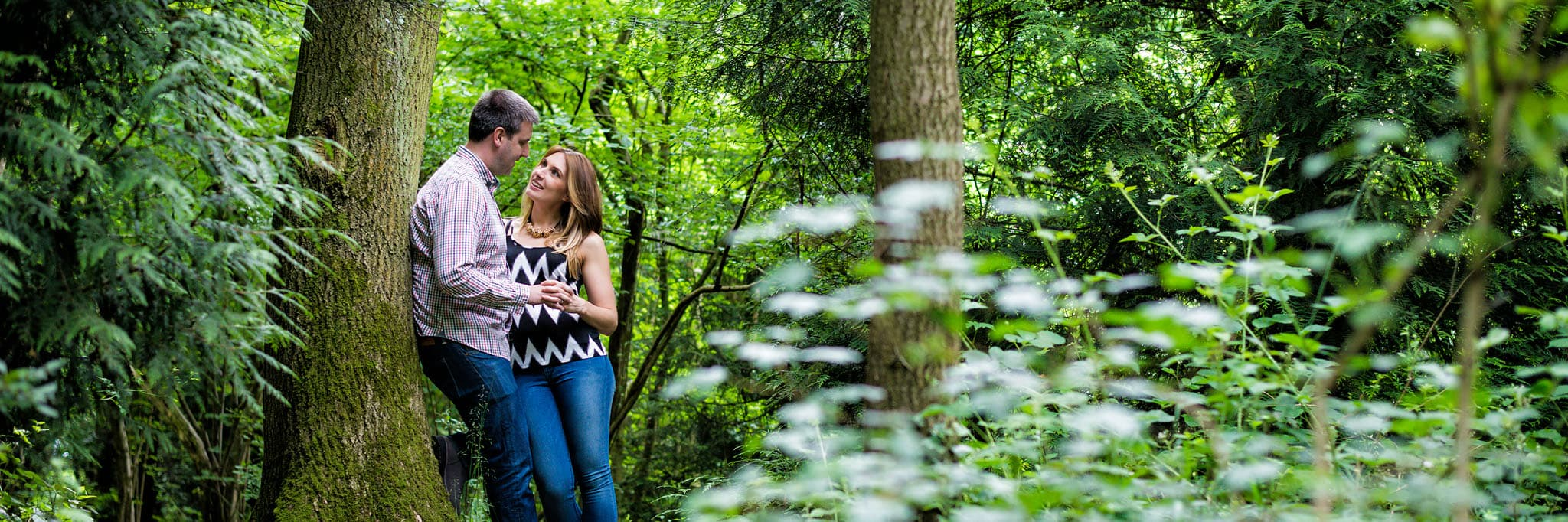 couple looking into each other's eyes in the woods during a pre-wedding shoot