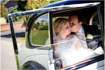 groom kissing his bride in their wedding car