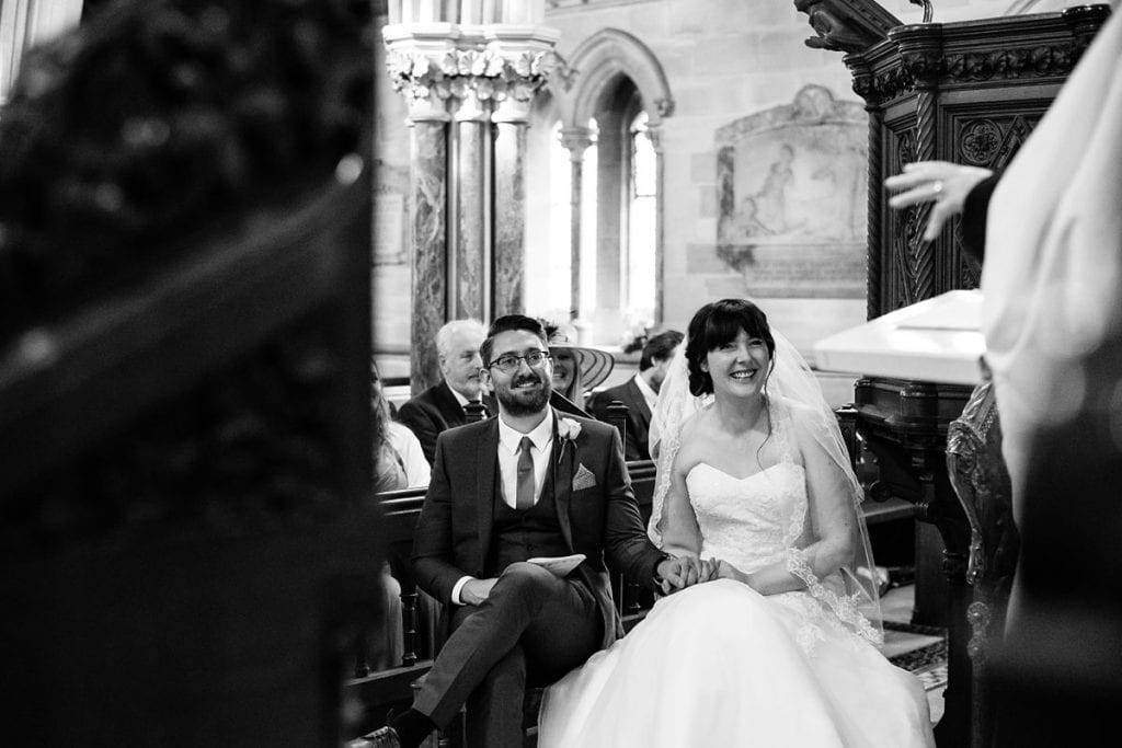 a smiley bride and groom during their church ceremony