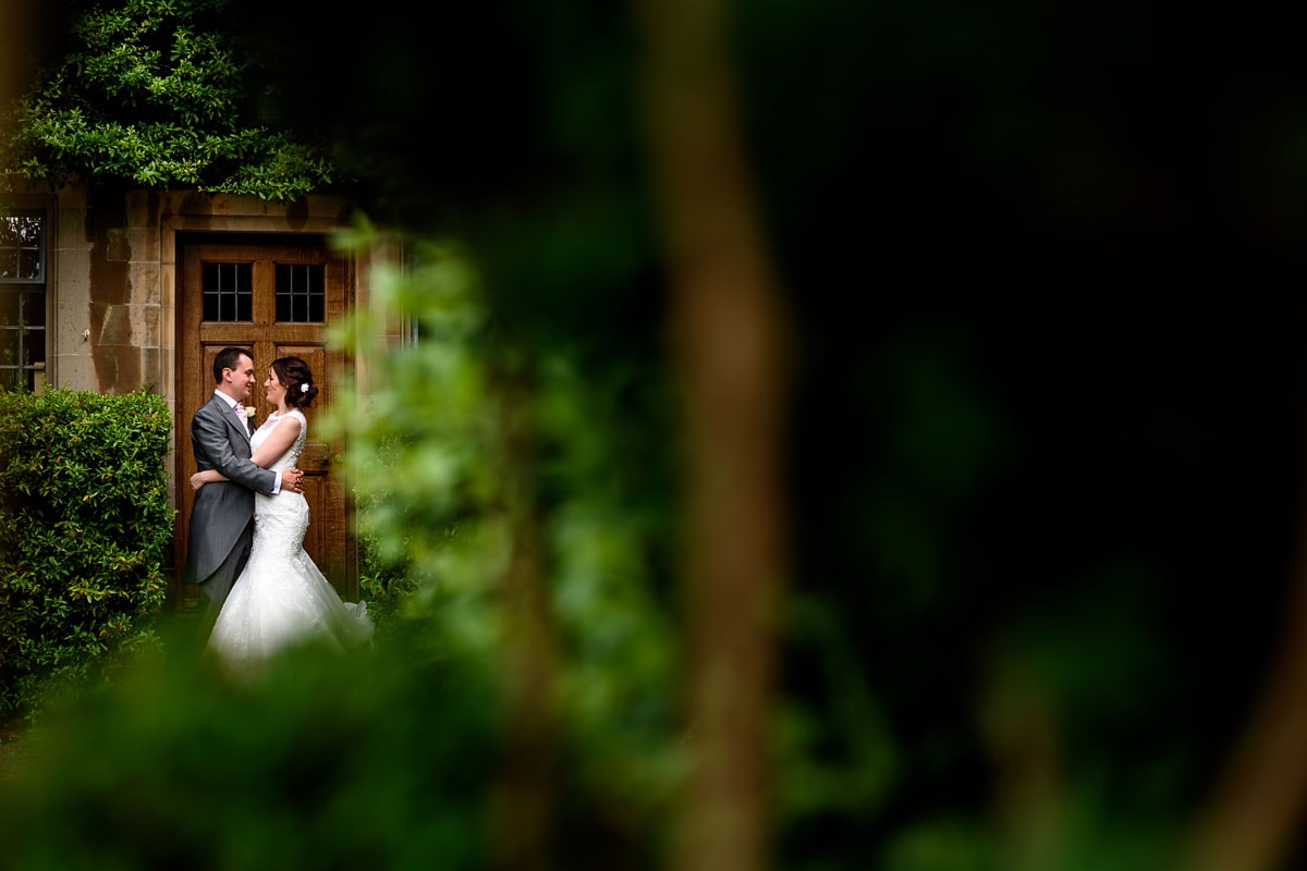 bride and groom framed by the bushes outside mallory court