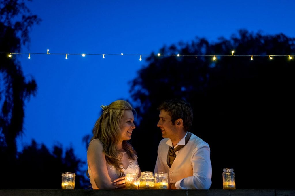 bride and groom lit by candles and fairy lights
