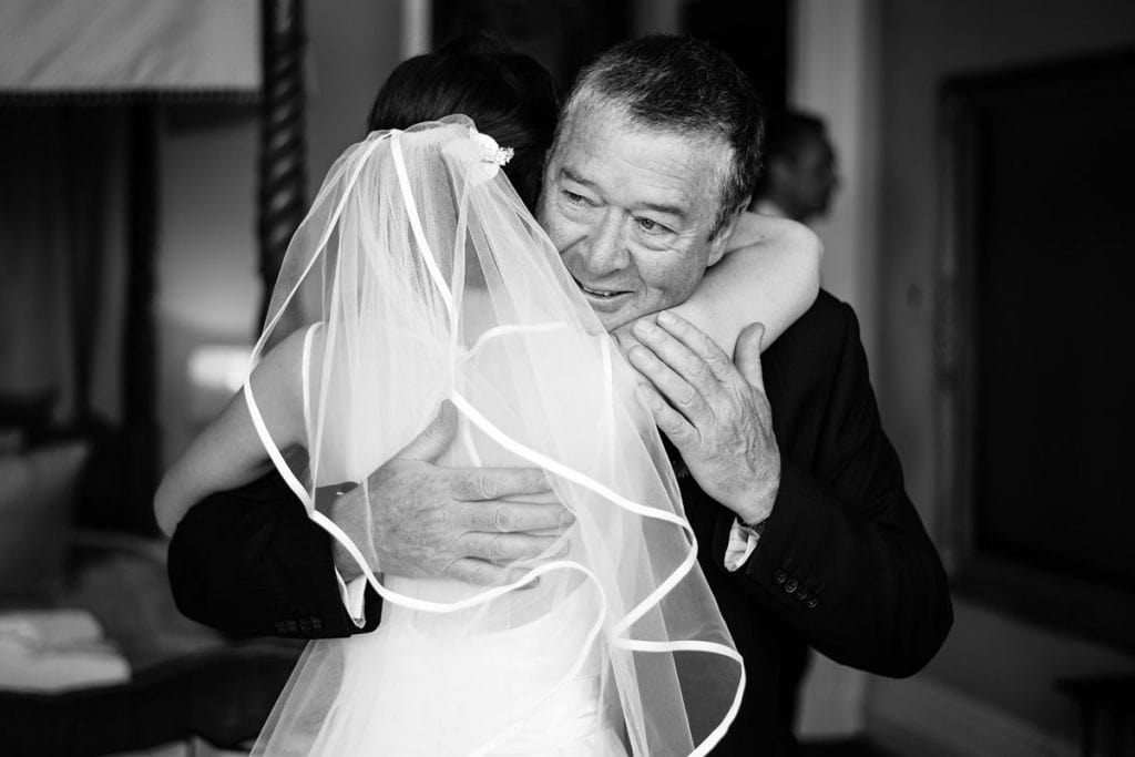 an emotional father of the bride hugging his daughter