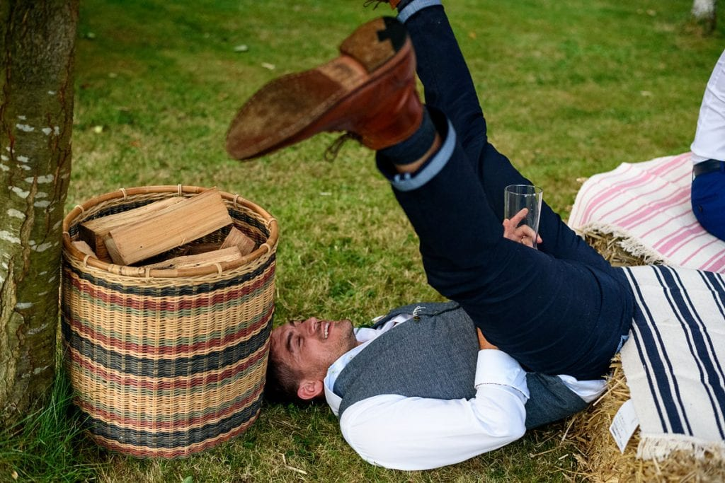 groomsman fallen off a hay bale but saving his drink