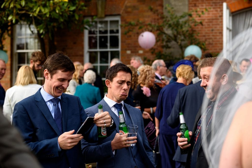 wedding guests messing about and enjoying a beer