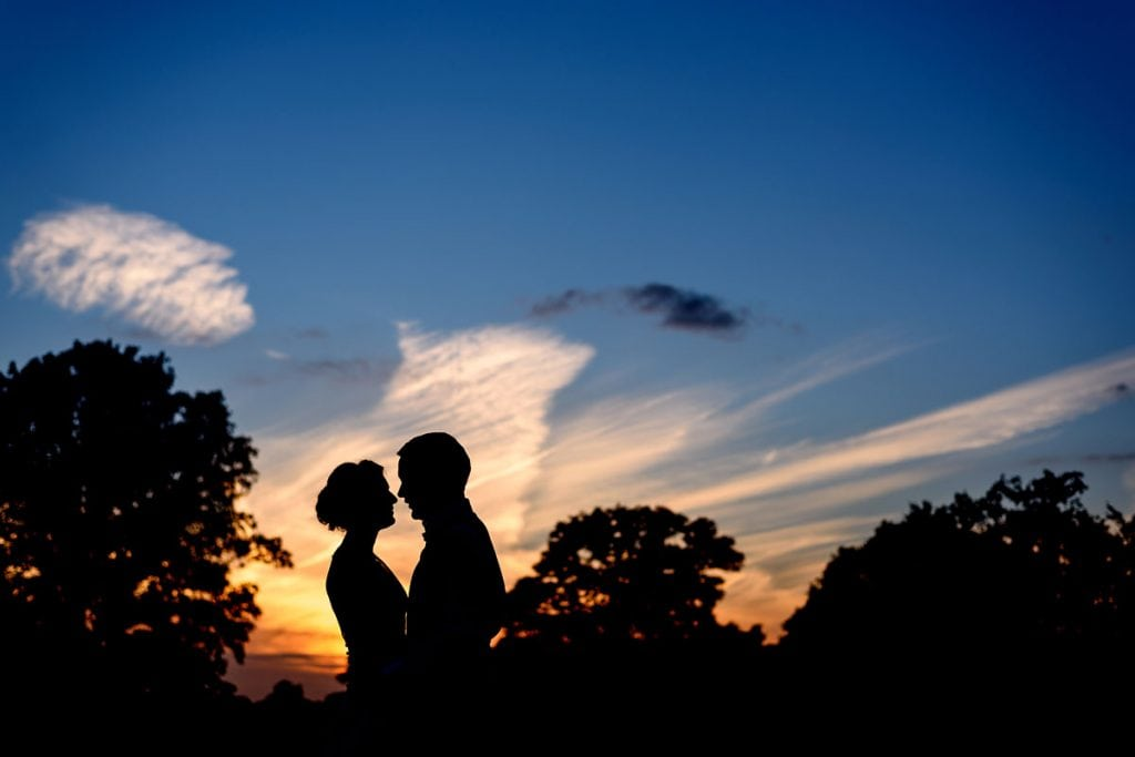sunset silhouette of the bride and groom during a summer wedding