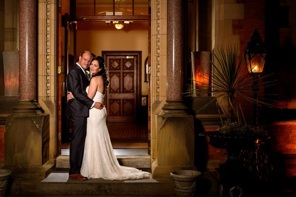 bride and groom outside the front of wroxall abbey in the evening
