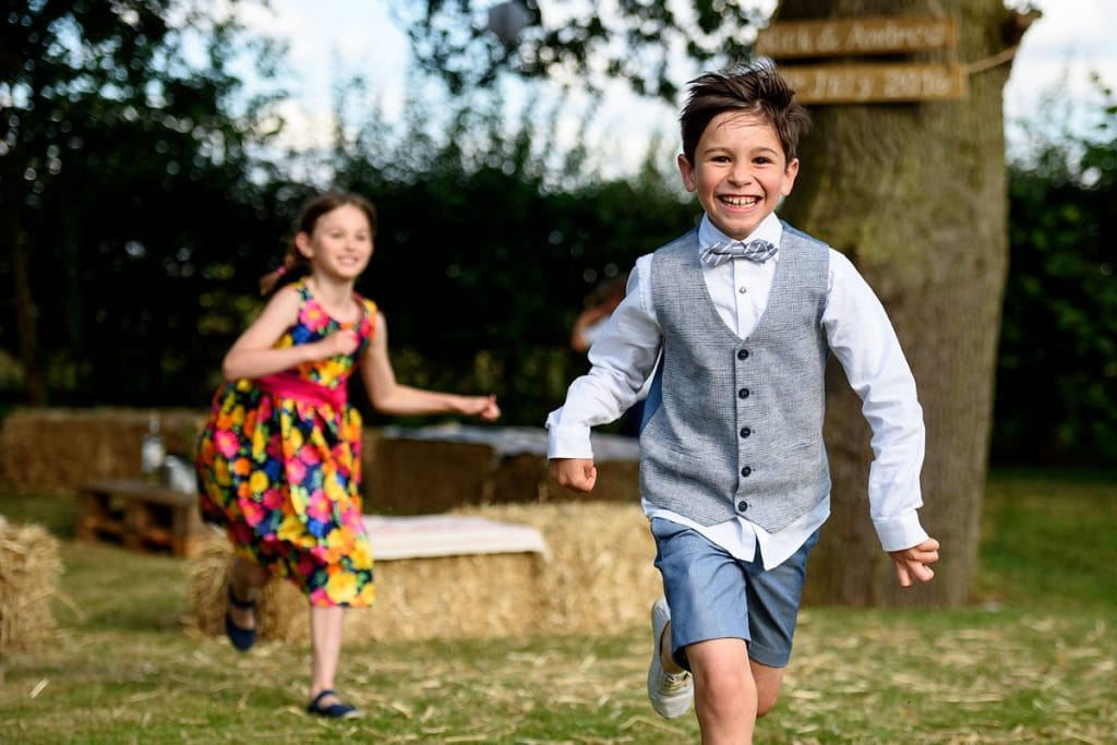 children running and playing outside during a summer wedding