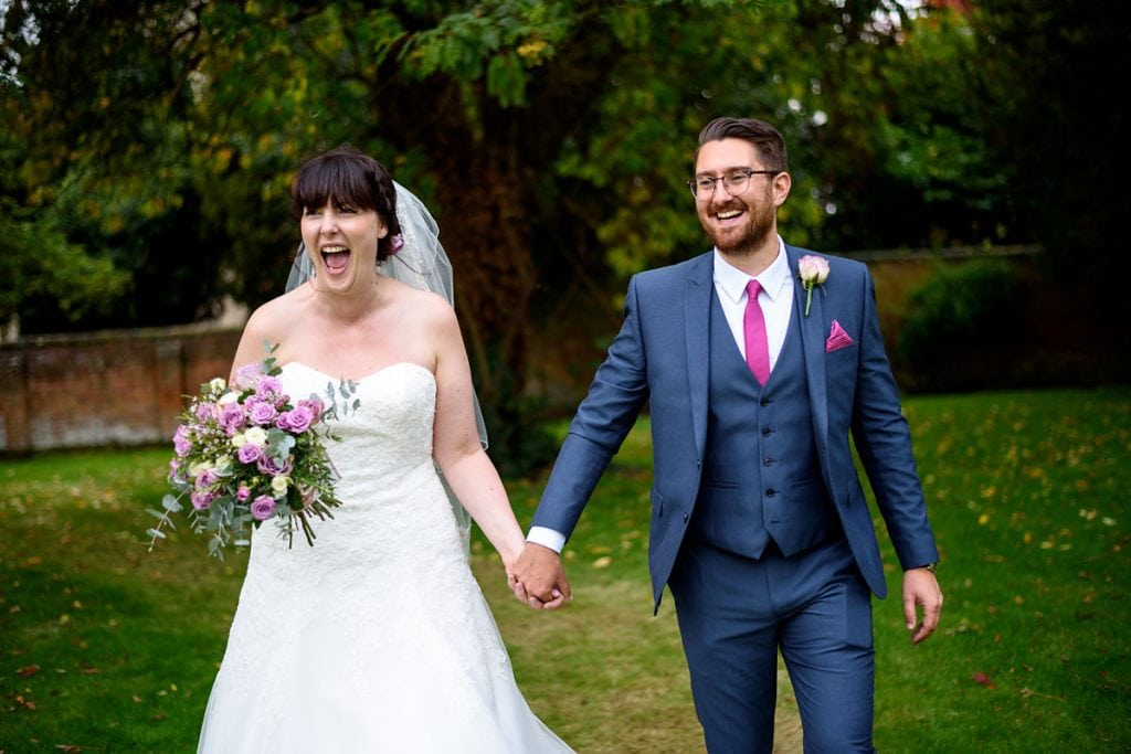 a very happy bride and groom walking through the gardens