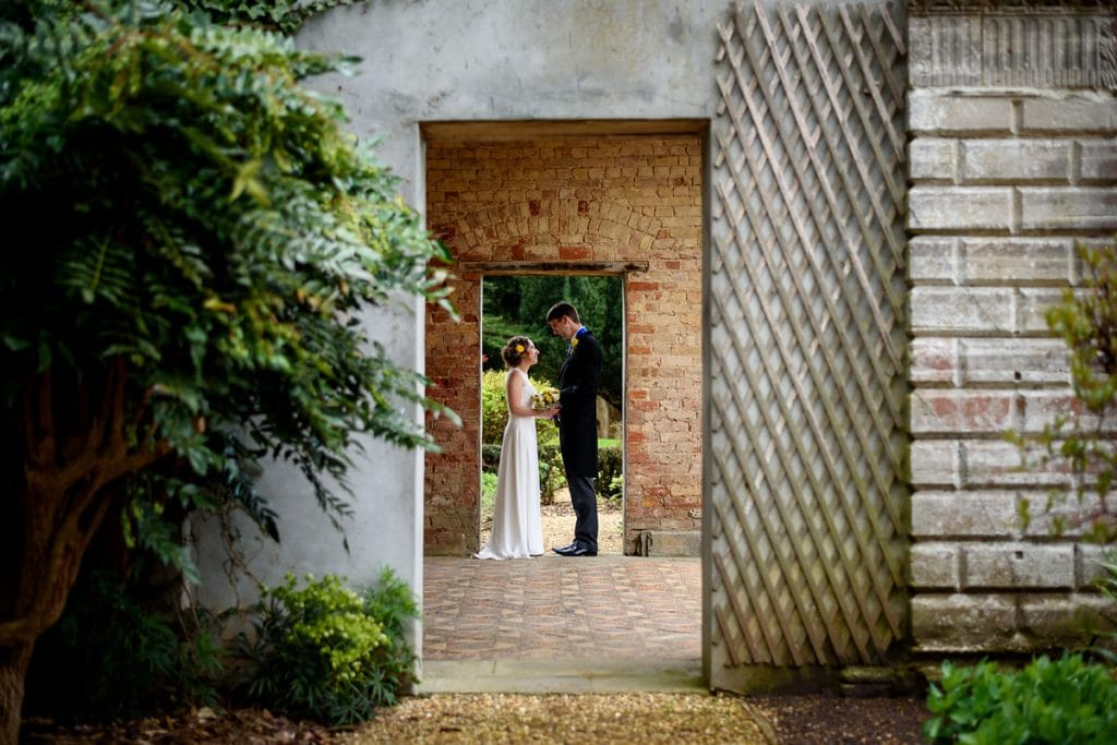 bride and groom framed by the orangery doorways at ettington park hotel