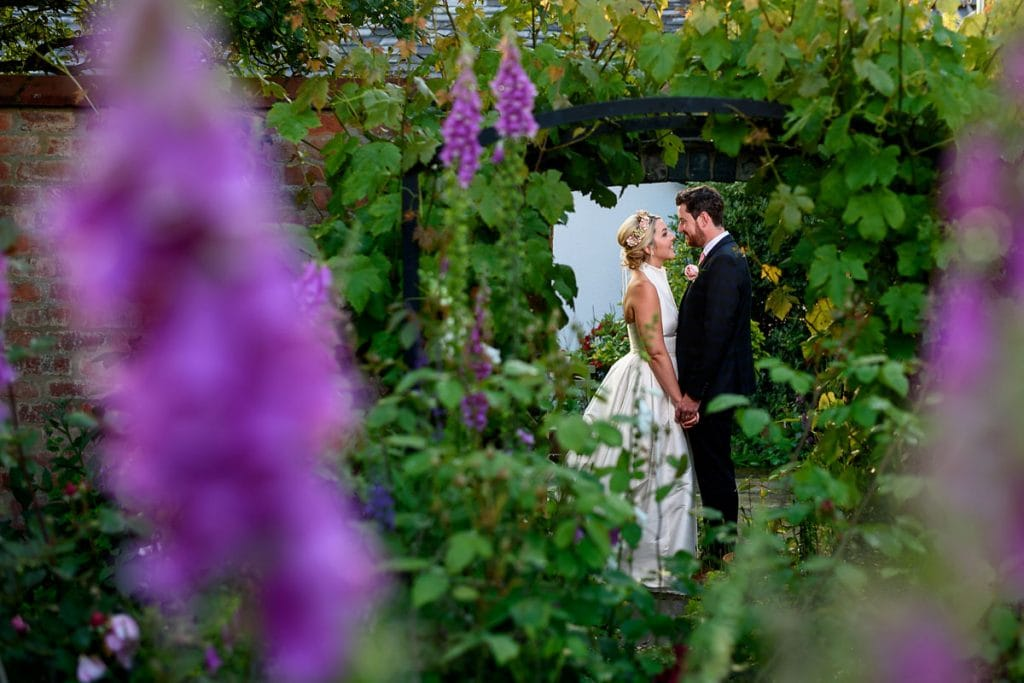 bride and groom photographed through the foxgloves in the summer garden