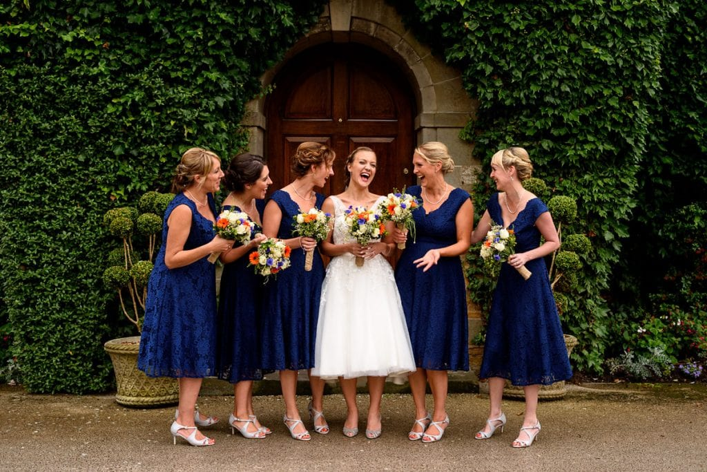 bride and bridesmaids sharing a joke outside mallory court