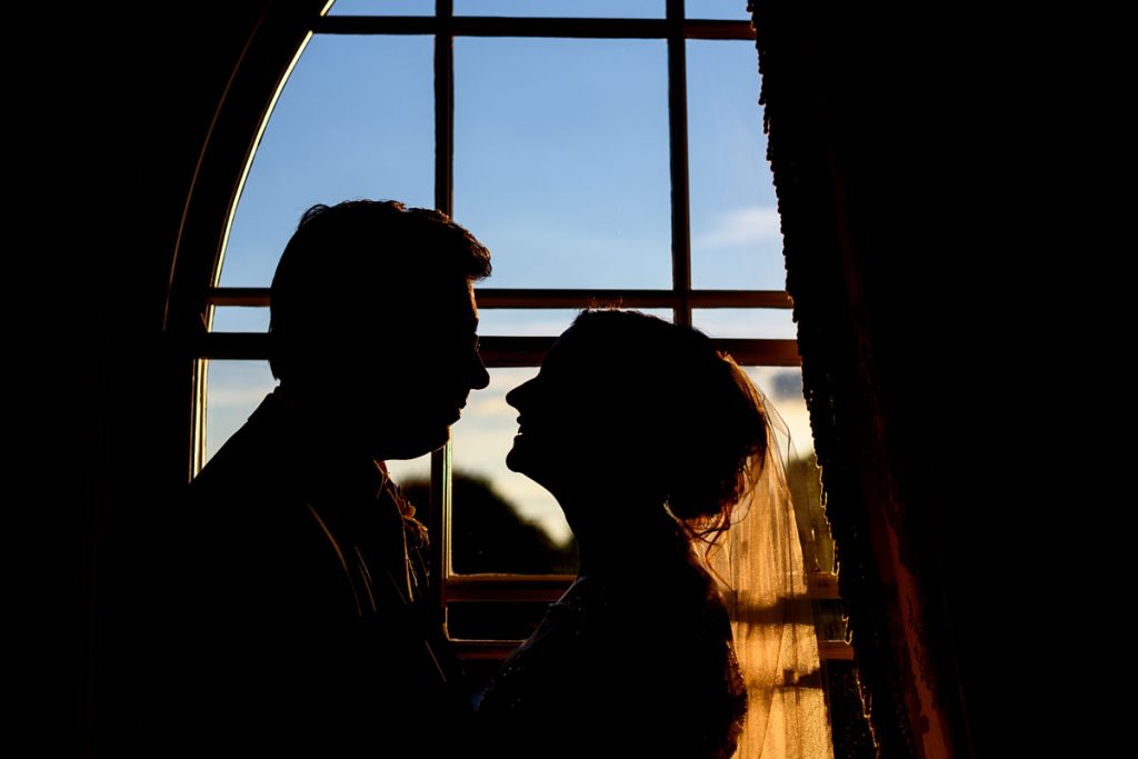 silhouette of the bride and groom in a window at warwick house