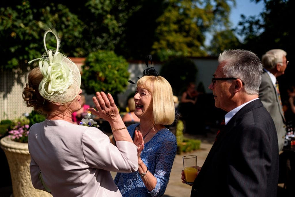 wedding guests laughing in the sunshine at warwick house