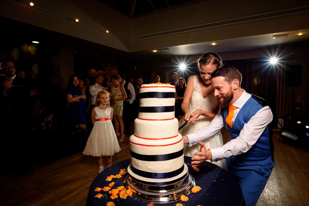 the groom protecting the wonky wedding cake whilst the bride cuts it