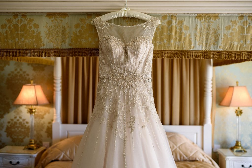 wedding dress hung on the end of the four poster bed