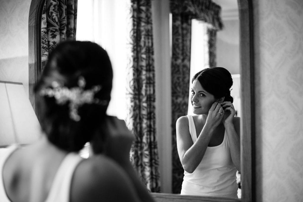 mirror reflection of the bride putting her earrings in
