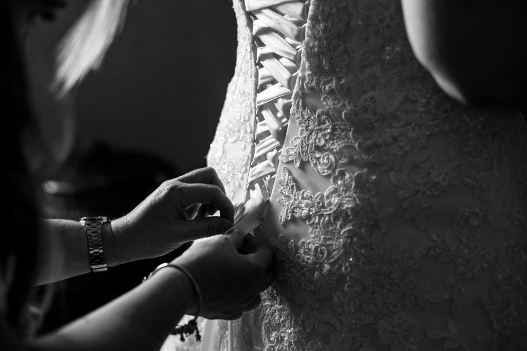 wedding dress being laced up in the window light