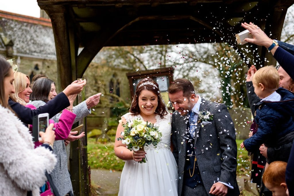 couple getting showered with confetti outside the church