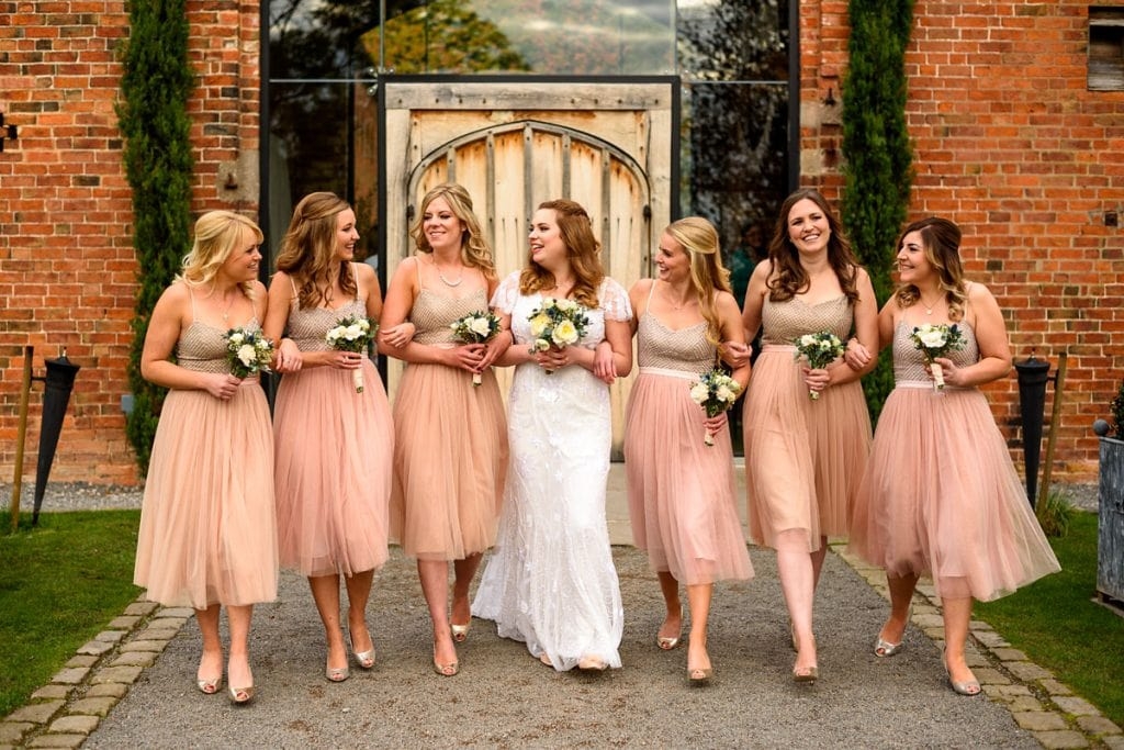 bride and her bridesmaids walking together outside shustoke farm barns