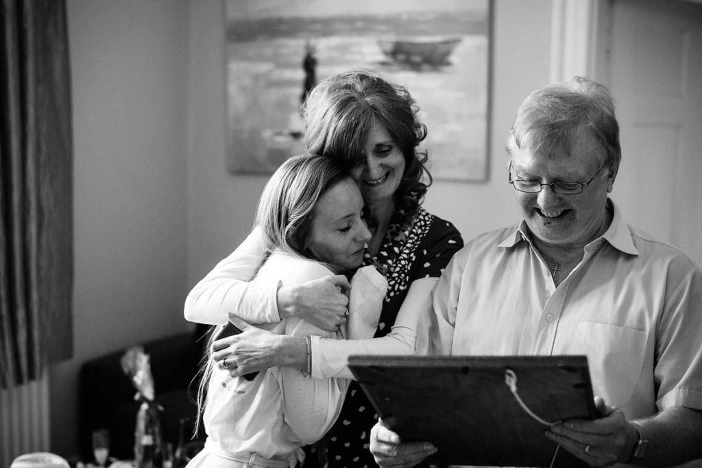 bride being hugged my her mum whilst her dad smiles looking at a picture