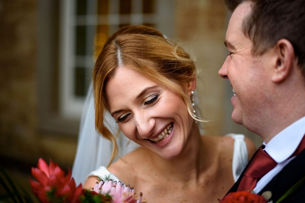 bride and groom laughing together outside compton verney