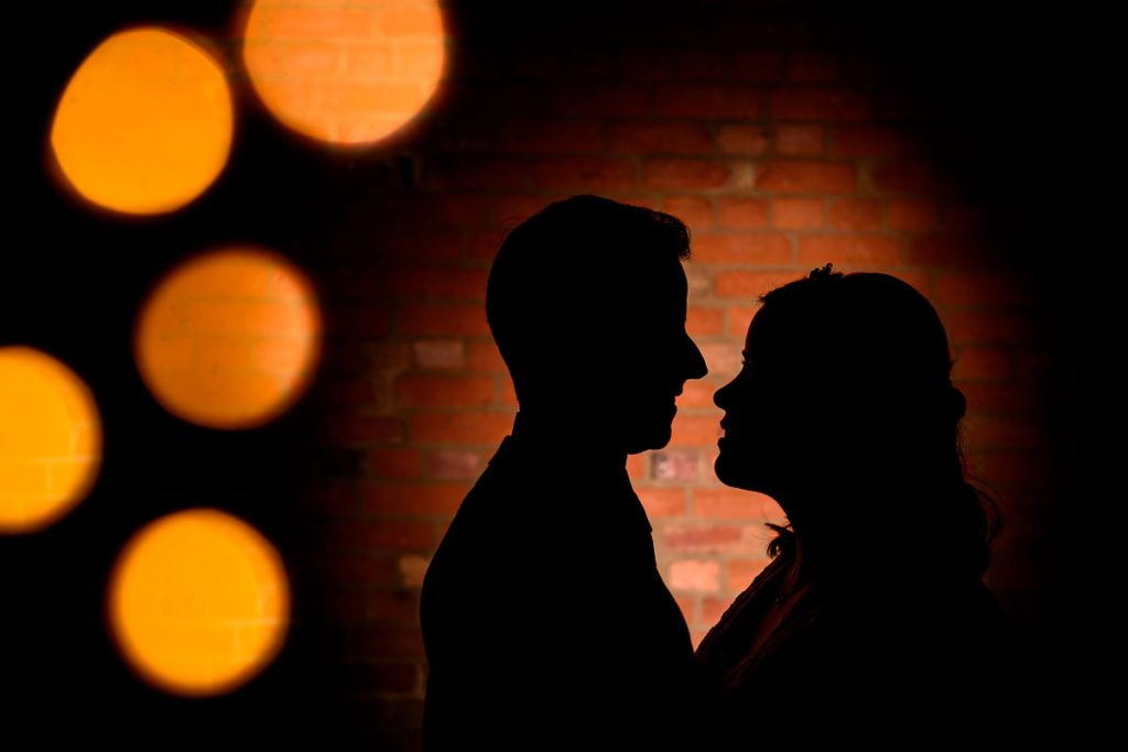 silhouette of the bride and groom with fairly light bokeh
