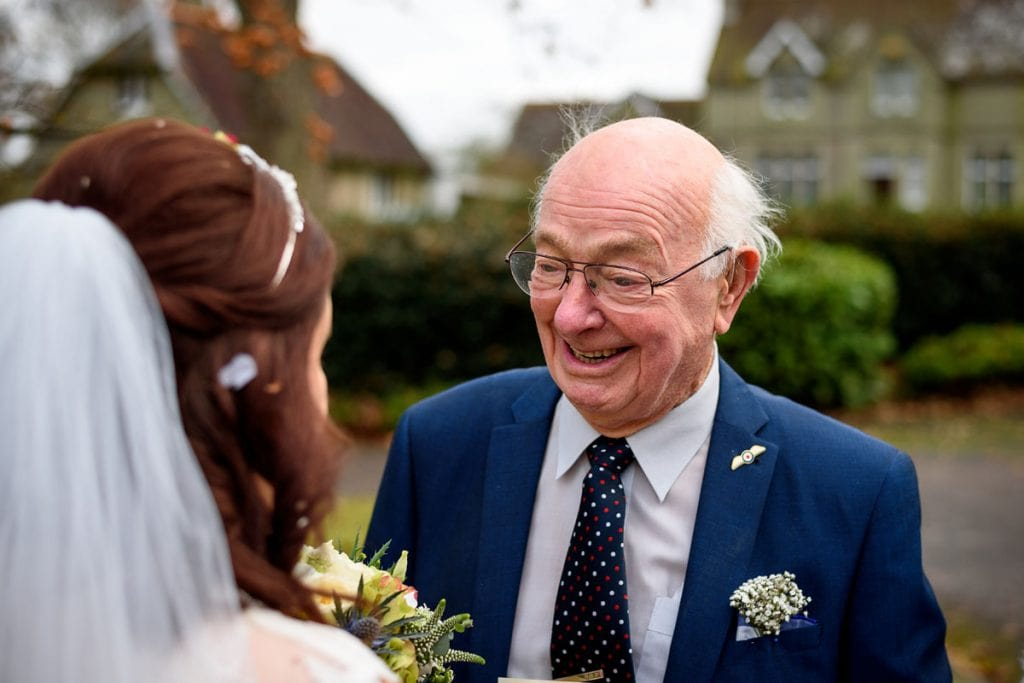 the bride's grandad looking at her with pride outside the church