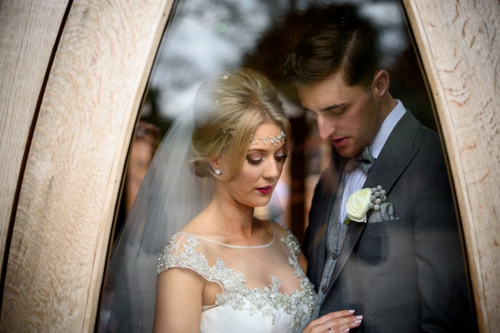 the bride and groom sharing a moment in the windows at shustoke farm barns