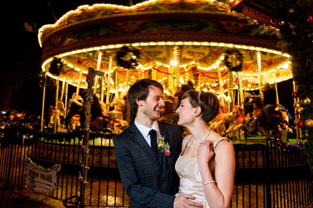 bride and groom smiling at each other at the birmingham christmas market