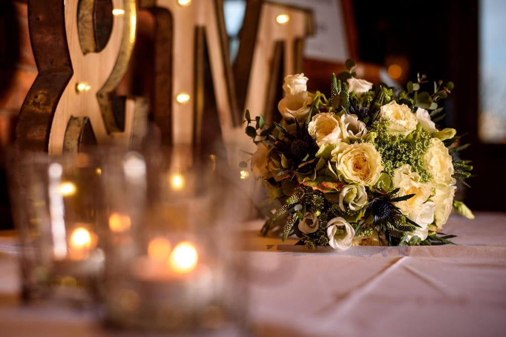 wedding bouquet with the twinkle of candles in the foreground