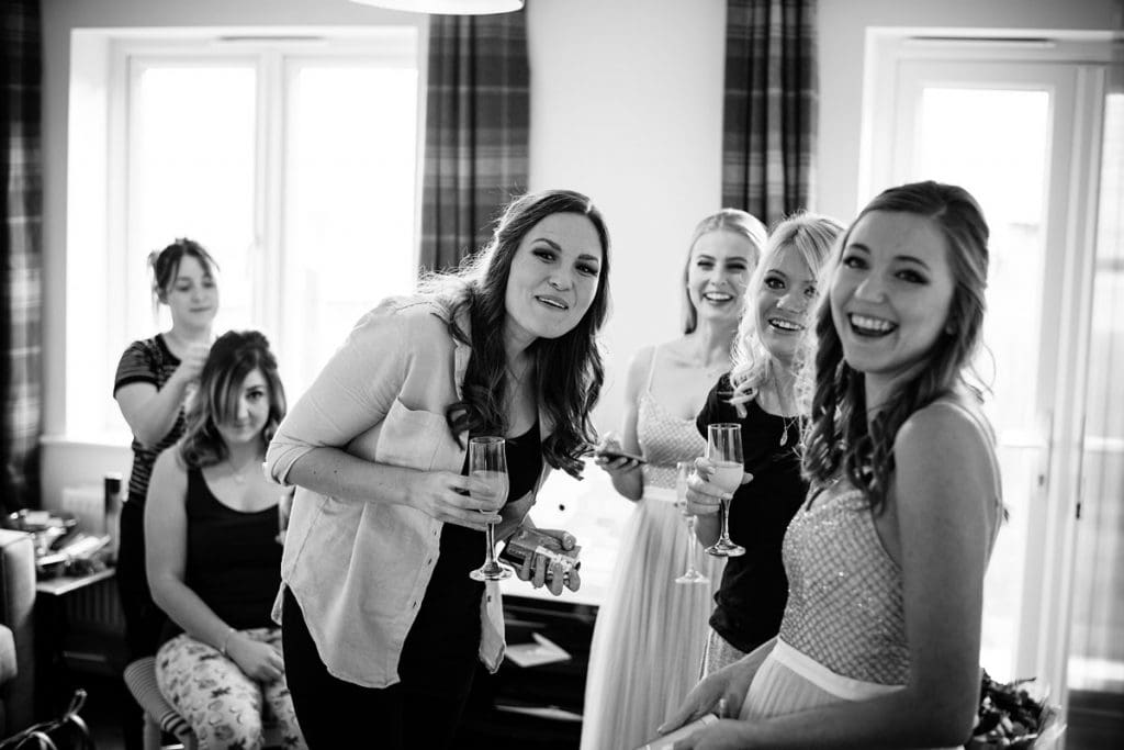 bridesmaids smiling as the father of the bride arrives