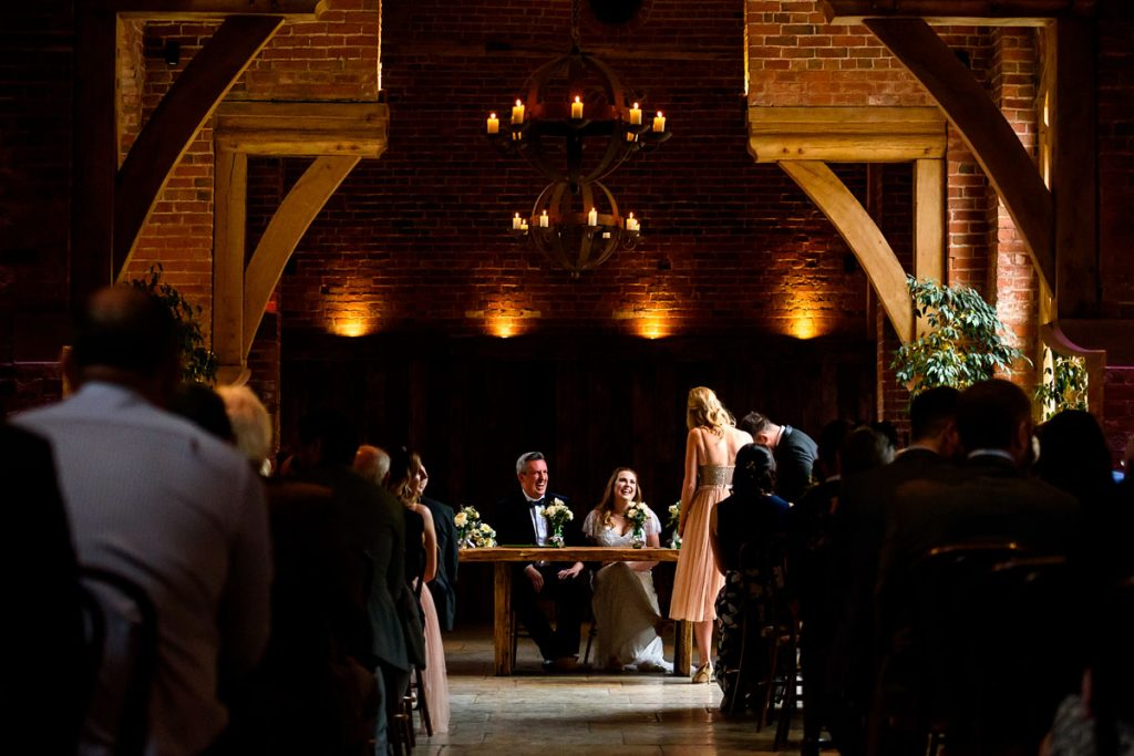 bride and groom laughing together as their witnesses sign the register