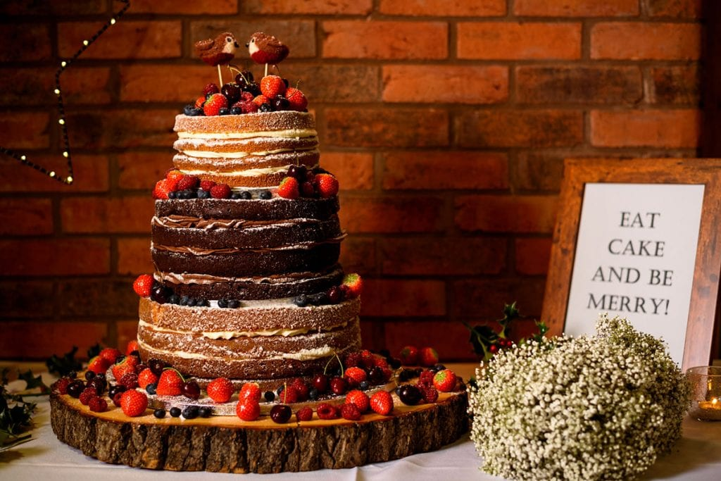 stunning naked wedding cake covered in berries