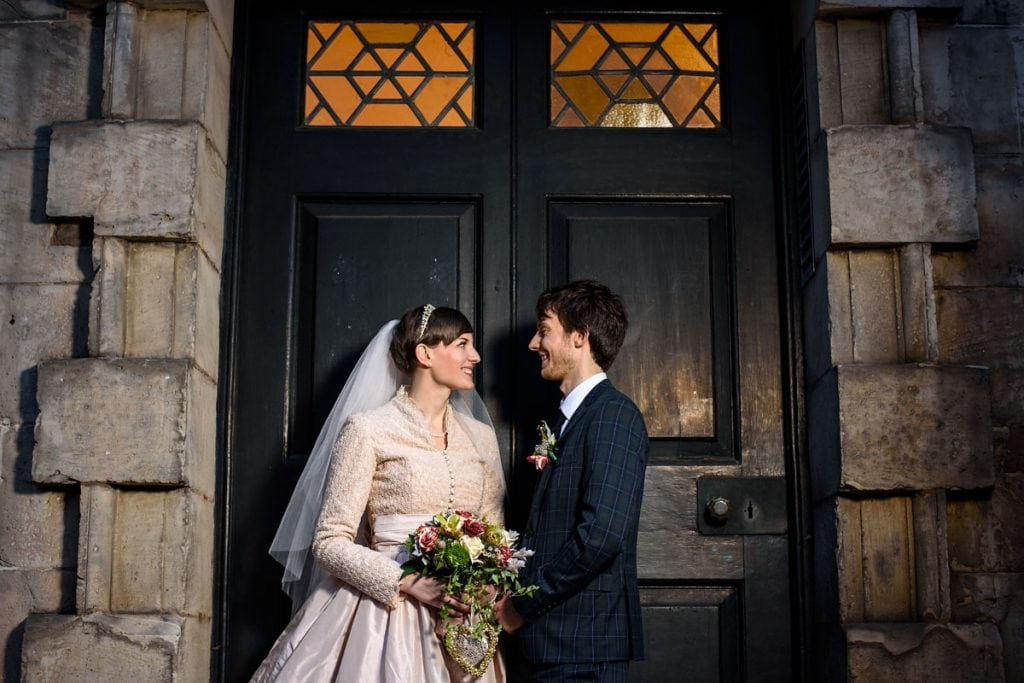 bride and groom smiling towards each other outside st paul's church in birmingham