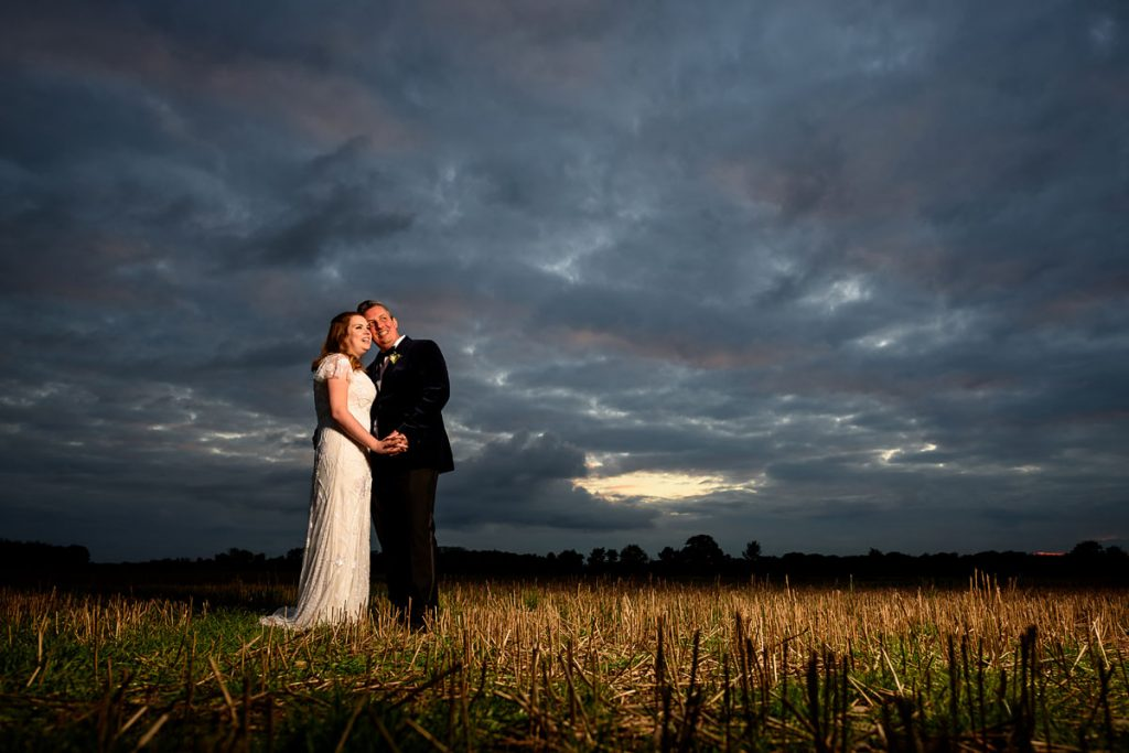 dramatic bride and groom portrait in the fields outside shustoke farm barns