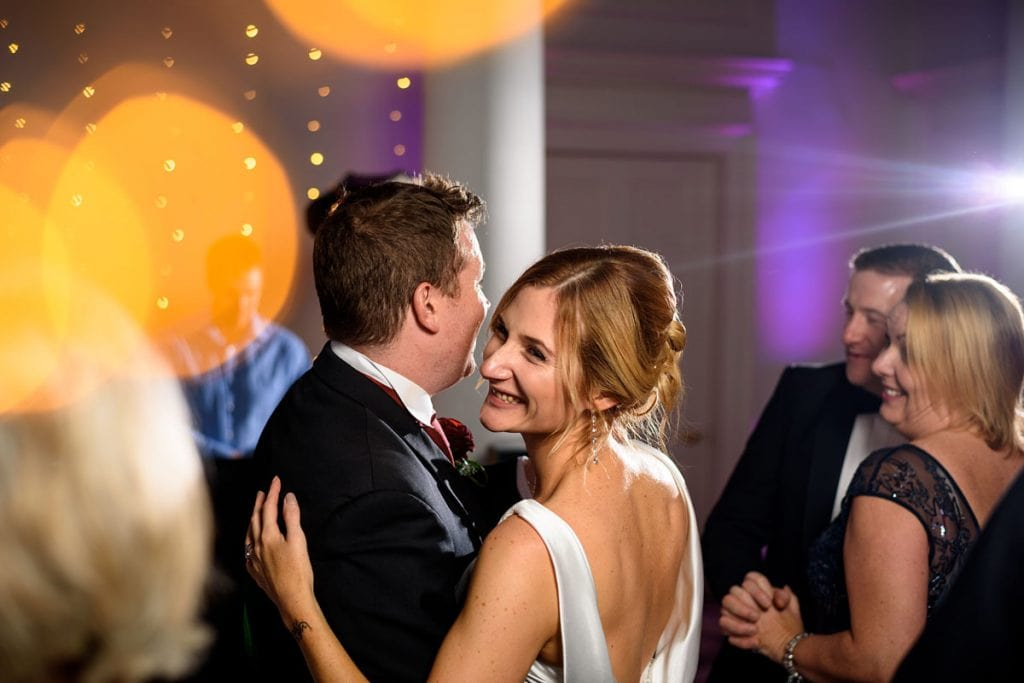 a smiley bride dancing with her husband on the dance floor at compton verney