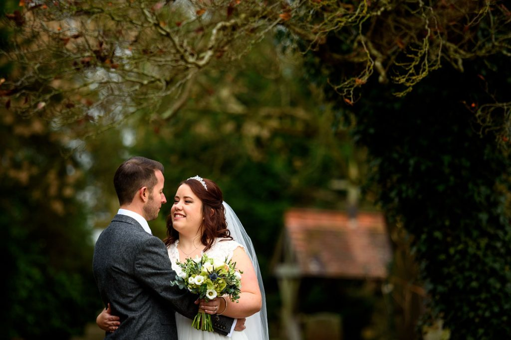 bride and groom portrait in the churchyard during their winter wedding