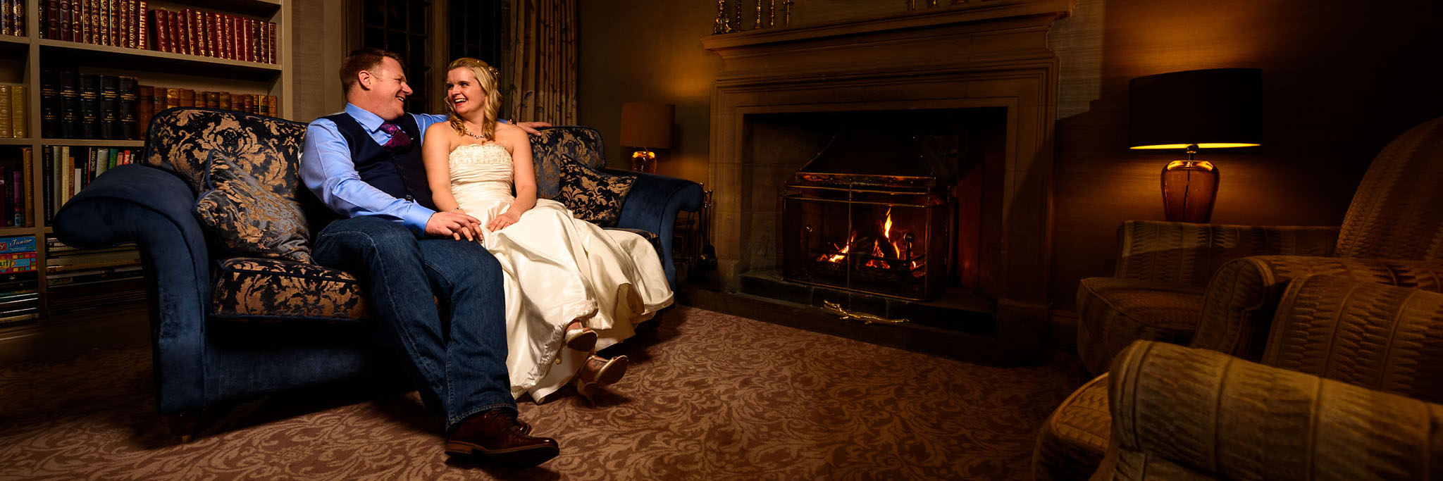 bride and groom sat cosied up on the sofa next to the fire