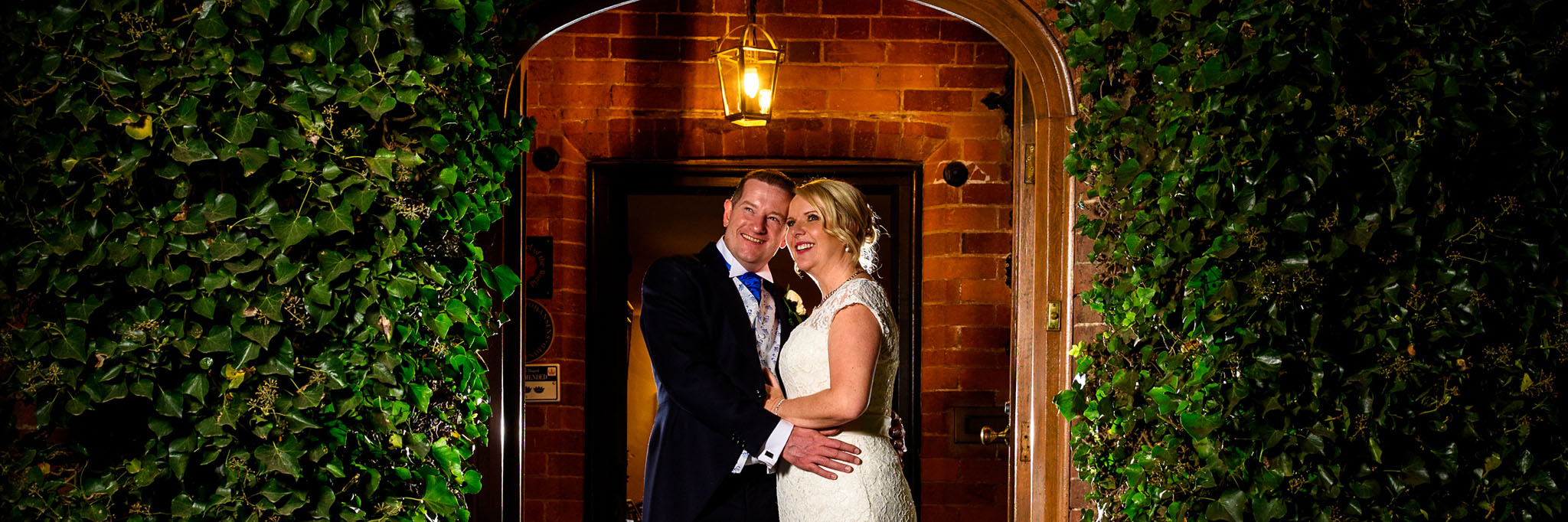 night time portrait of the bride and groom in the doorway of nailcote hall