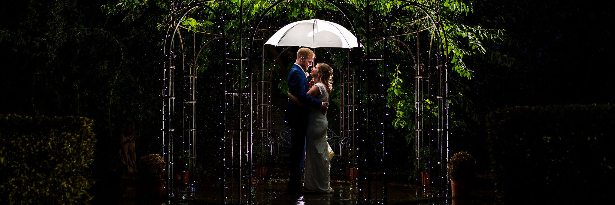 bride and groom portrait under an umbrella at night