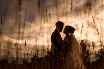 evening silhouette of the bride and groom in a field of long grass