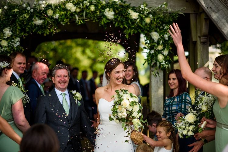 laughing bride and groom showered with confetti