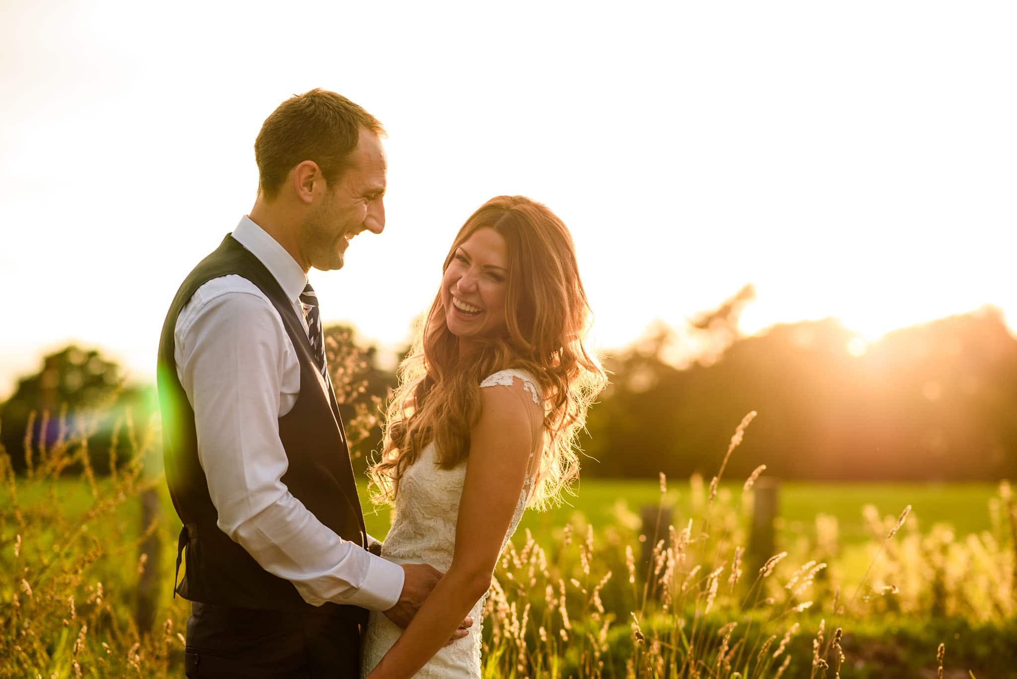 bride and groom laughing in the evening sunshine