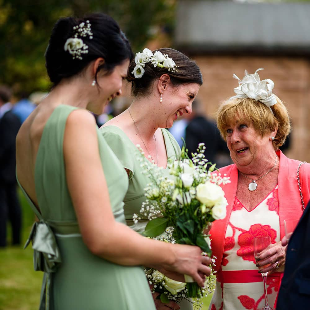 bridesmaids sharing a joke with the mother of the groom
