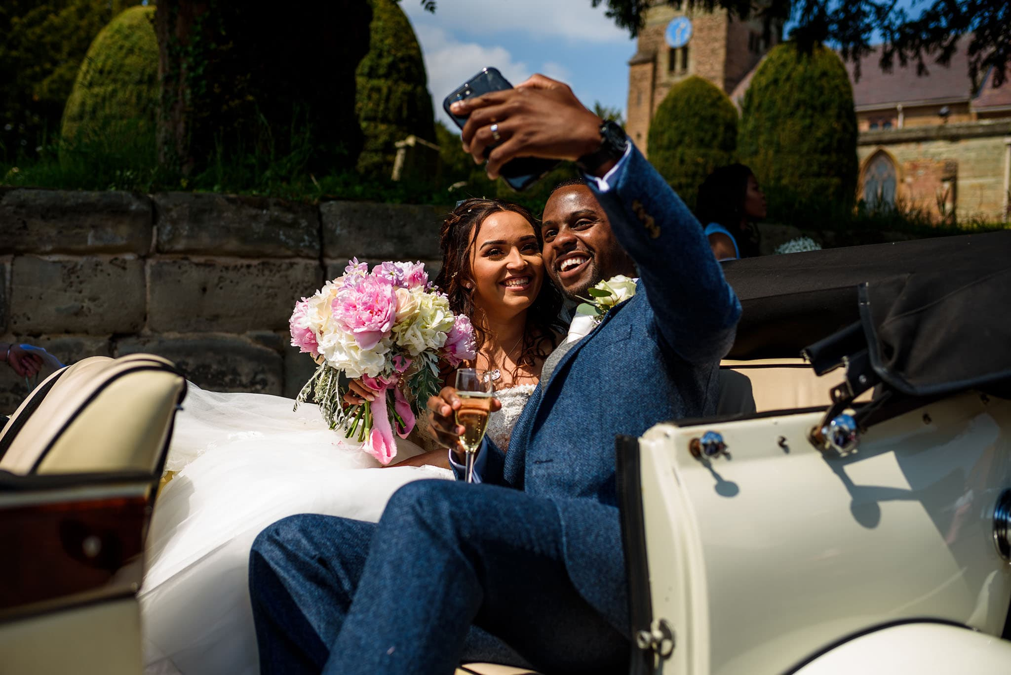 bride and groom selfie in their vintage wedding car