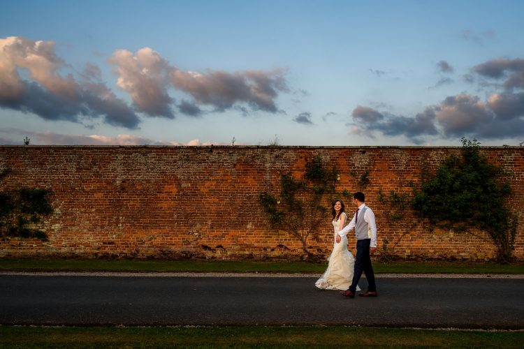 bride and groom walking together during sunset