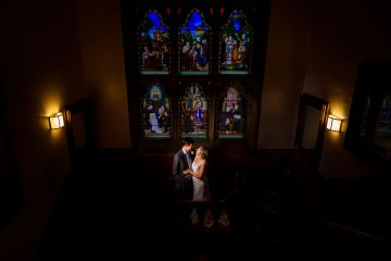 intimate portrait of the bride and groom next to the stain glass window in wroxall abbey