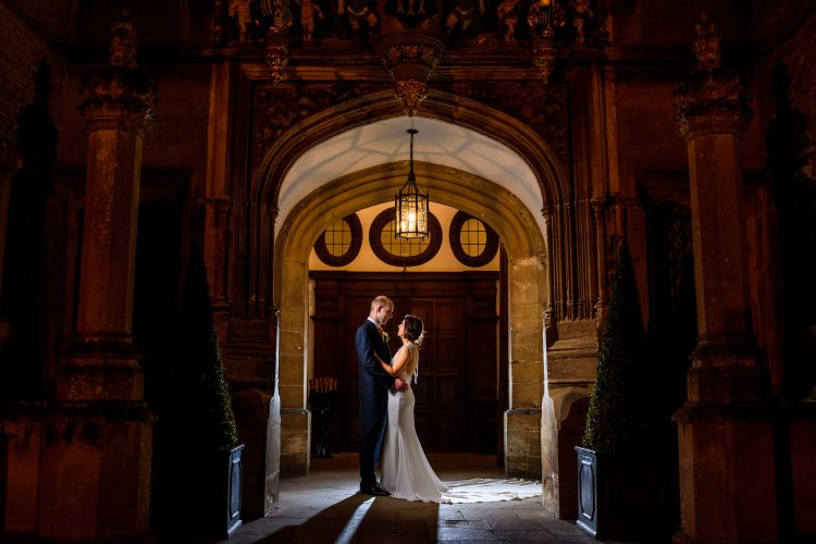 bride and groom night time portrait in the entrance to Hengrave Hall